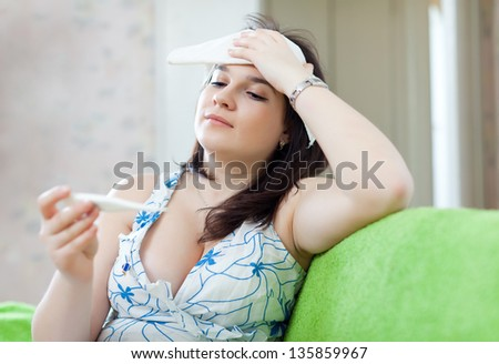 Sick woman with thermometer stupes  towel to her head