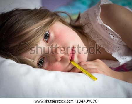 Sick young girl with a thermometer - stock photo