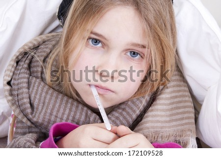 Sick young girl with thermometer in bed