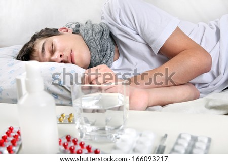 Sick Young Man sleeping on the Bed near the table with a pills