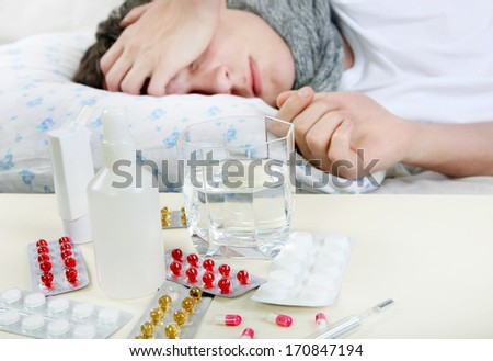 Sick Young Man sleeps with Pills on foreground. Focus on the Pills - stock photo