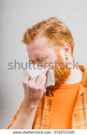 Sick young man with running nose - stock photo
