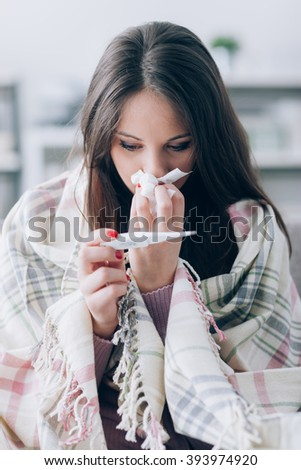 Sick young woman at home on the sofa, she is covering with a blanket, taking temperature and blowing her nose with a tissue - stock photo