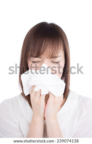 sick young woman blowing her nose isolated on white background