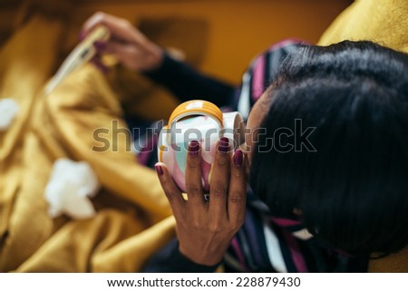 Sick young woman blowing her nose on the sofa