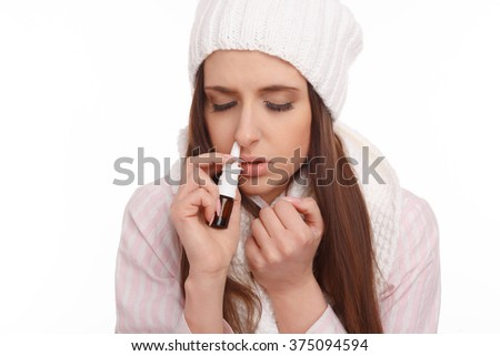Sick young woman in pajamas scarf and hat use nasal spray. Woman applies nasal spray isolated. Sick Woman.Flu.Woman Caught Cold.