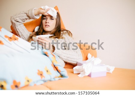 Sick young woman lying on sofa measuring body temperature - stock photo