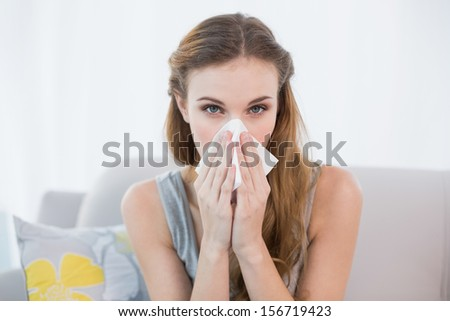 Sick young woman sitting on sofa blowing her nose at home in the sitting room