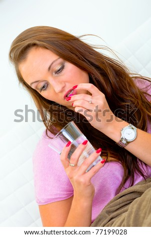 Sick young woman taking pill and holding glass of water - stock photo