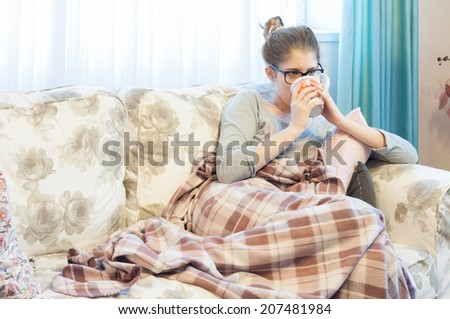 Sick young woman with headache sitting on the sofa and drinking tea. Girl with flu symptoms feeling tired. The flu and Ebola virus share similar symptoms, including headache, fever and fatigue. - stock photo
