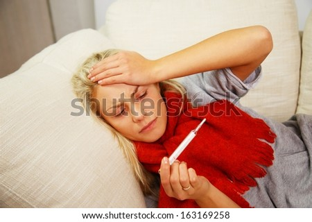Sick young woman with thermometer lying on sofa at home - stock photo