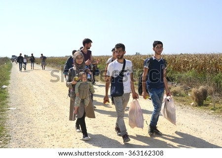 Sid, Serbia - September 18th, 2015: Syrian family walking on the dirt road, preparing to cross the border between Serbia and Croatia, looking for a new life. Mother, father and child going to EU.