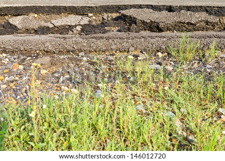 Side asphalt road broken due to collapsing ground until the grass grows  - stock photo