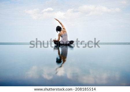 side bend, side stretching with swimming pool view - stock photo
