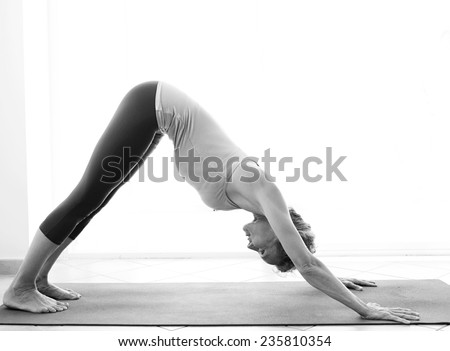 Side black and white view of a mature healthy sporty woman using a yoga mat to stretch her body in a light and airy interior. Fit professional woman exercising and stretching her body, indoors. - stock photo