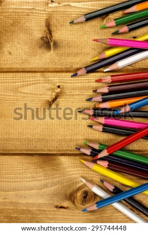 Side border of colorful pencil crayons against a wood background - stock photo