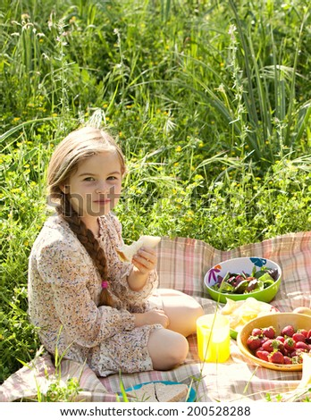 Side close up portrait of a young caucasian girl sitting in a sunny field of grass and flowers having a picnic and enjoying a summer holiday. Eating healthy, relaxing activities lifestyle, outdoors. - stock photo