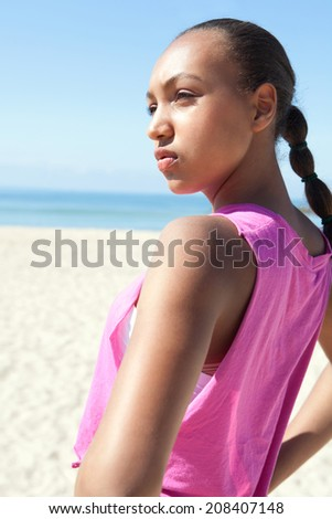 Side close up portrait of an attractive healthy black young woman standing on a white sand beach relaxing on vacation during a sunny day contemplating the sea, outdoors. Sporty recreational lifestyle. - stock photo
