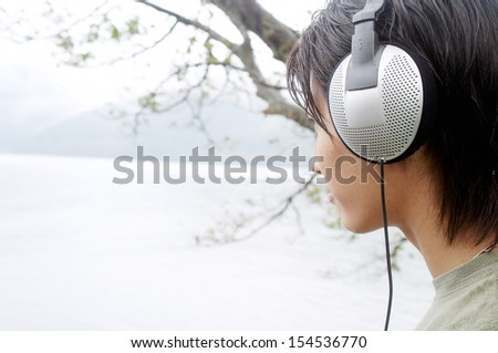 Side close up portrait of an attractive japanese man listening to music with his headphones contemplating a lake in the japan mountains landscape during a rainy day, relaxing. - stock photo