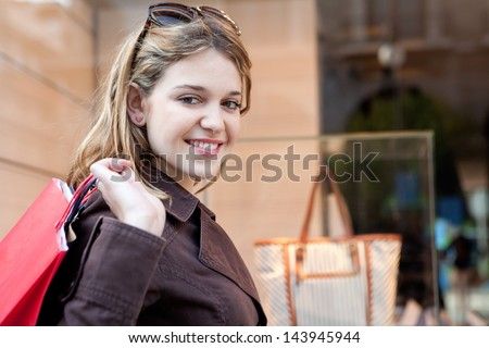 Side close up portrait view of a young attractive consumer woman visiting the fashion stores in the city, walking past a shopping display window and carrying paper bags, smiling. - stock photo