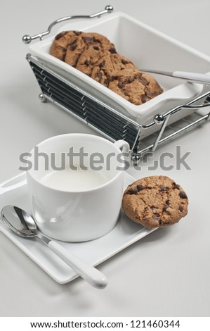 Side closeup view of biscuits in white ceramic plate with spoons and cup of milk on white wooden background - stock photo