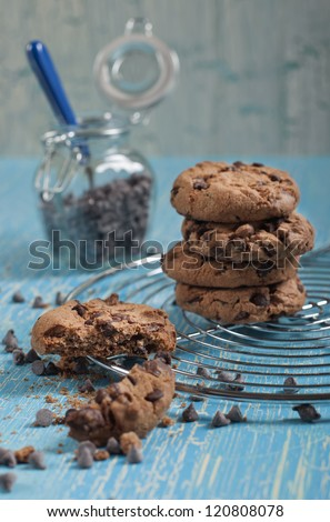 Side closeup view of cookies with chocolate drops on round iron stand, jars with chocolate drops on cracked blue background - stock photo