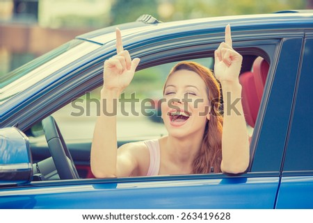 Side door view woman driver happy smiling showing thumbs up sitting inside new blue car  outside on parking lot background. Beautiful young woman happy with her new vehicle. Positive face expression - stock photo