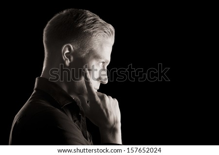Side-face low key portrait of young attractive man in dark shirt with hand at chin looking straight, black and white, isolated on black background.