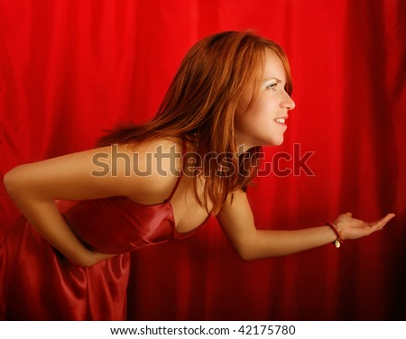 Side half body portrait of young woman taking bow on stage with red curtains in background.