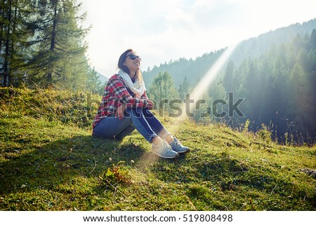 Side low angle shot of happy Caucasian woman who is sitting on the grass on the mountain peak and looking at the sky. Wearing sunglasses