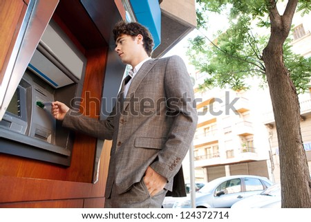 Side low view of an elegant businessman withdrawing money from a wood decorated bank cash point, outdoors. - stock photo