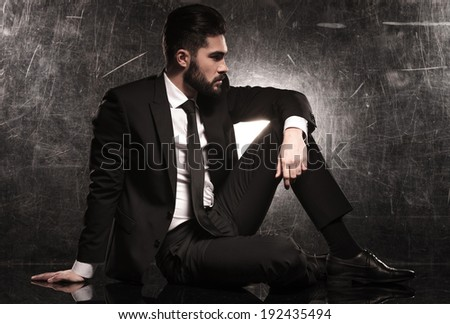 side of an elegant business man in black suit and tie looking away