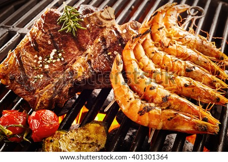Side of beef garnished with rosemary and salt next to prawns and tomatoes roasting on flaming grill - stock photo