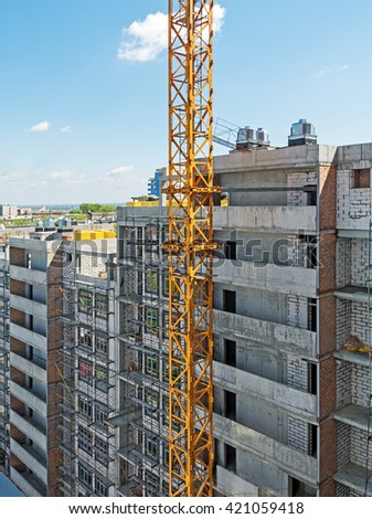 Side of of a house construction high-rise multilevel building with right angles amid crane - stock photo