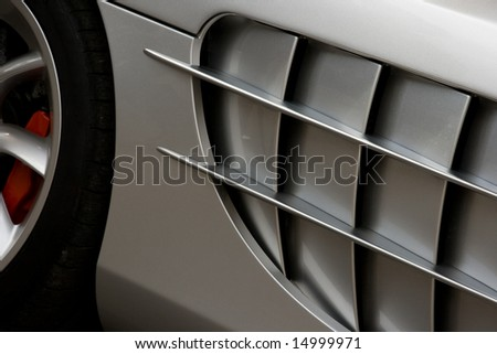 Side of silver super car with large cooling vent