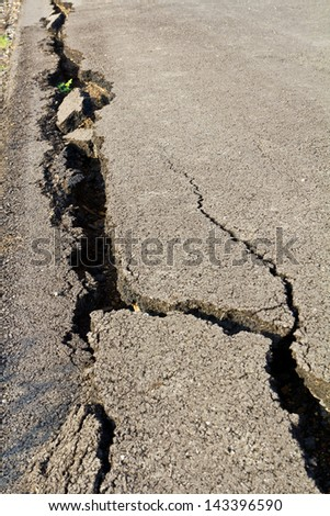 Side of the asphalt road surface crack due to ground collapsing. - stock photo