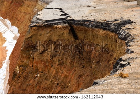 Side of the broken asphalt road collapsed and fallen, since the ground collapsing.