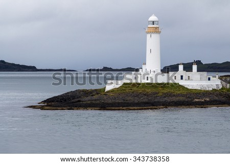 Side of the white lighthouse of Lismore framed by a gray sea and sky, near Mull and Oban, in the Inner Hebrides of Scotland. The lone beacon gives guidance, warning, safety to ships near the coast. - stock photo