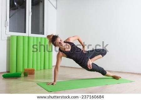 Side plank with half lotus yoga pose - stock photo