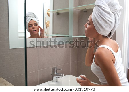 Side portrait and face reflection of a beautiful young woman applying nourishing cream on her face, looking at herself in a bathroom mirror, with towel wrapping her hair, home interior. Skin care. - stock photo