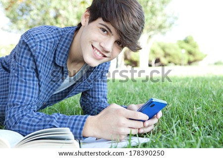Side portrait close up view of a young teenager student boy laying down in a park studying with his college books and using a smartphone to browse the internet, smiling. Technology lifestyle. - stock photo