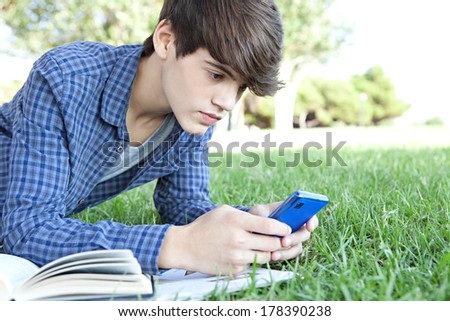 Side portrait close up view of a young teenager student boy laying down on green grass in a park studying with his college books and using a smartphone to browse the internet. Technology lifestyle. - stock photo