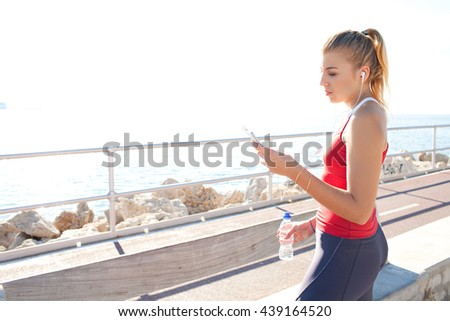 Side portrait of a beautiful adolescent young woman listening to music on smart phone and holding a bottle of mineral water, relaxing from exercising, beach outdoors. Sport and technology lifestyle. - stock photo