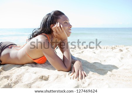 Side portrait of a beautiful african american woman laying down on a white sand beach by the shore, relaxing while on a summer vacation. - stock photo