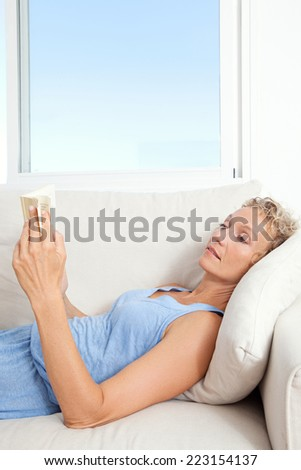 Side portrait of a beautiful middle age healthy woman laying down on a white sofa at home, holding and reading a book indoors. Woman relaxing and home living lifestyle.