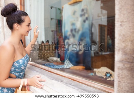 Side portrait of a beautiful smiling teenager girl looking at clothes in a fashion store holding shopping bags, outdoors. Adolescent consumer shopping in city, recreation lifestyle.