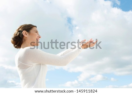 Side portrait of a beautiful young woman holding her hands together up in the air with space in the blue sky offering something imaginary, conceptual image. - stock photo