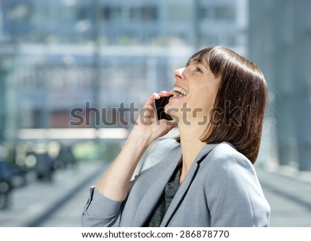 Side portrait of a business woman laughing and talking on cell phone