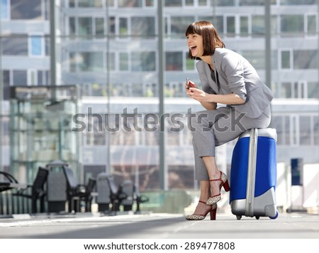 Side portrait of a business woman sitting on suitcase and laughing with mobile phone - stock photo