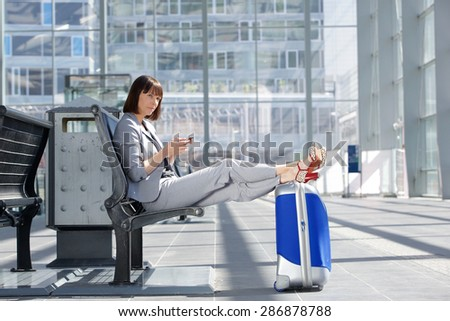 Side portrait of a business woman sitting with cell phone and bag at airport - stock photo